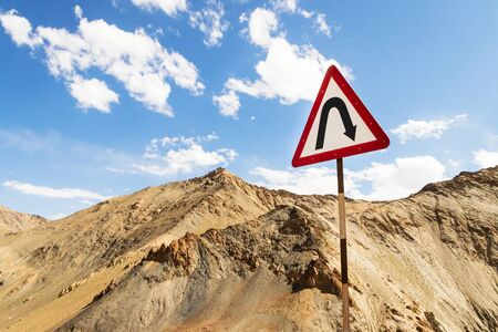 Curves ahead highway sign in Leh Ladakh, Jammu and Kashmir, India. Traffic sign with mountain and blue sky background. Stock Photo