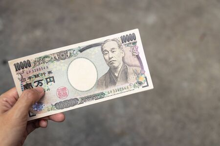 Ten thousand Japanese Yen banknotes on hand isolated on grey background.