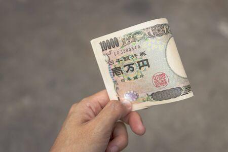 Ten thousand Japanese Yen banknotes on hand isolated on grey background. 版權商用圖片