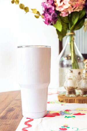 White tumbler glass cold store. Stainless steel tumbler mug on table. No plastic with reuse item; save world.