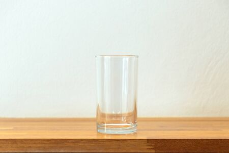 Empty glass of water on a wooden table and white wall with soft sunlight through a window. Reklamní fotografie