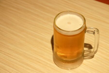 Cold mug of beer with foam and water drops on wooden table.
