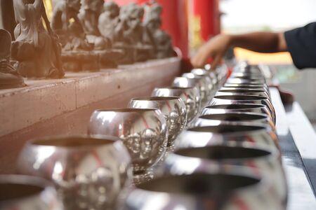 Buddhist is donate a money in a Buddha statue's alms little bowl at Wat Boromracha Kanchanapisek Anusorn (or Wat Leng Noei Yi 2) ; chinese temple.