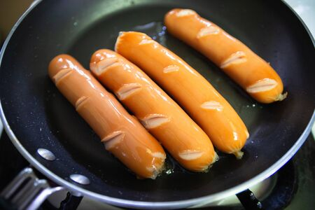 Sausages on frying pan. Quick and easy meal. Stock Photo