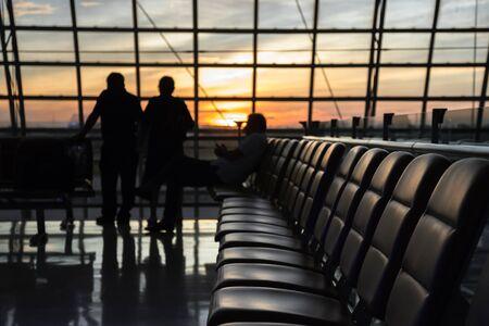 Silhouet van een luchthaven bij zonsondergang. Stoelen voor wachtende vluchten op de luchthaven. Concept van zaken en reizen in moderne lounges. Stockfoto