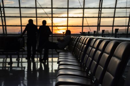 Silueta de un aeropuerto al atardecer. Asientos para espera de vuelos en el aeropuerto. Concepto de negocios y viajes en salones modernos. Foto de archivo