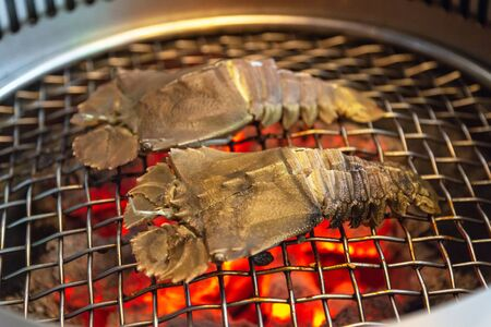 Mantis prawns on a gridiron over flaming grill.