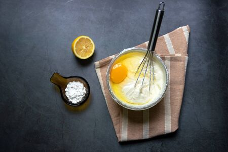 Chef whisking cream with egg in glass bowl with flour and lemon on kitchen table for delicious cheesecake. Standard-Bild