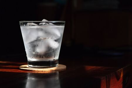 Glass of water with ice cubes on wooden table; shades of sunlight through from window.
