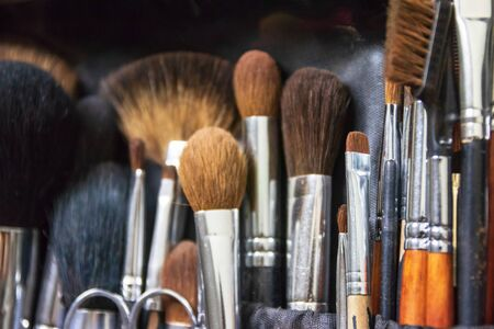 Collection of professional makeup brushes in case; selective focus.