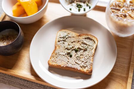 Chicken liver pate on bread with iced coffee, mango and soft boiled egg with seasoning sauce and ground pepper on wooden tray. Easy healthy breakfasts for your morning.