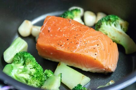 Cooking salmon steak on pan with broccoli and garlic. Grill salmon fillet.