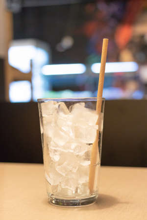 Paper straws in glass of ice cubes on wooden table at restaurant. Eco friendly straws.