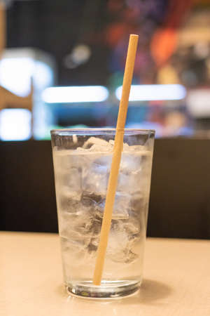 Paper straws in glass of water with ice cubes on wooden table at restaurant. Eco friendly straws.