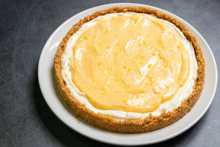 Delicious homemade honey lemon cheese pie and juicy lemon curd on plate with copy space on black table background.