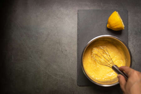 Chef whisking juicy lemon curd in a pot with copy space on black table background.