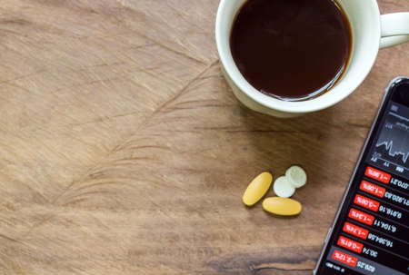 Black coffee and aspirin with a bad news in the morning. Stock market crash, analysis of the market data on smartphone.