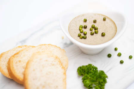 Chicken liver pate with fresh baguette on white mable plate.