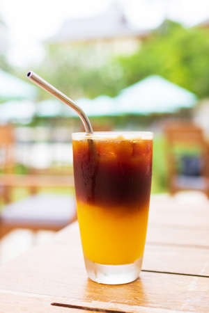 Iced fresh orange juice topped with espresso on wooden table in a garden; as sunrise coffee make a good day.