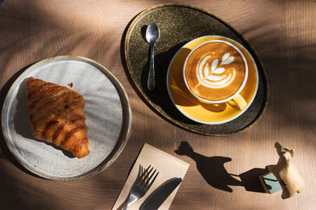 Cup of coffee with latte art with croissants on wooden table and morning sunlight with shadow through from window. Beautiful meal with warm sunlight. Standard-Bild