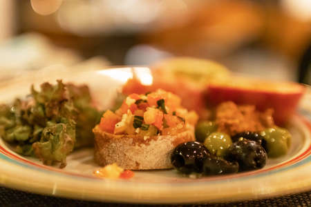 Classic Italian appetizer dish; bruschetta with heirloom tomatoes and olives in warm light romance restaurant dinner. Stock fotó