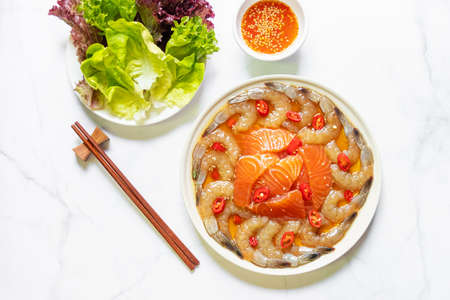 Pickled shrimp and salmon with soy sauce served spicy dipping sauce and vegetables on marble table background.