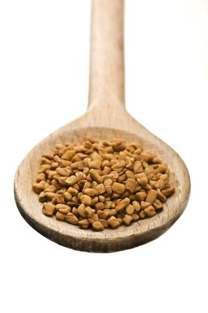 fenugreek: wooden spoon with fenugreek seeds isolated on white background
