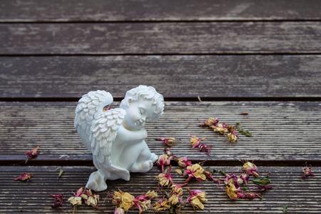 valentine cherub: white angel sculture on the wood floor