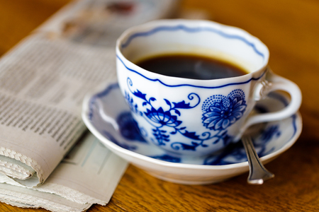 Decoration coffee cup in wood table with Newspaper.