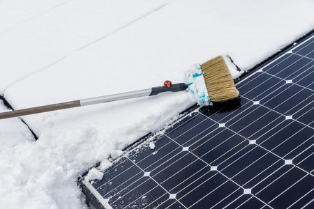 Photovoltaic panels on the roof cover with snow, with a bass-broom in the winter.
