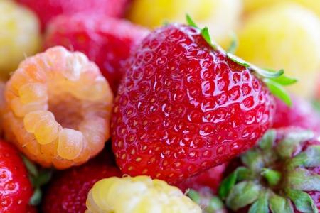 bio yellow raspberries with red strawberries. close up. Фото со стока