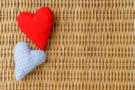 Valentine day, red and blue dotted handmade hearts on knitted rattan background.Valentines Day card.