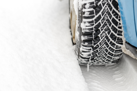 Car tyre in winter covered with snow.On road with fresh snow. close up. Фото со стока