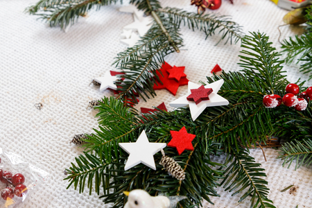 Decoration of handmade red and white advent christmas wreath from fir. Фото со стока
