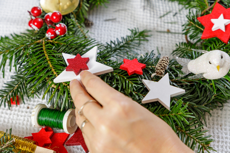 Hands of a woman decorate Christmas Advent wreath from fir twigs. Фото со стока