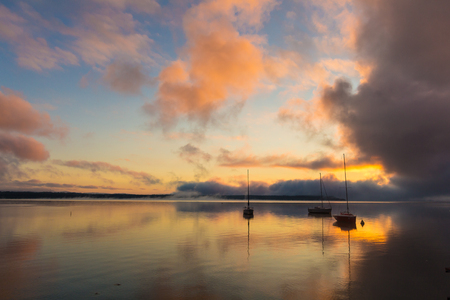 Sunrise on the lake with boats, reflection of sun in water, with fog and clouds on summer morning.