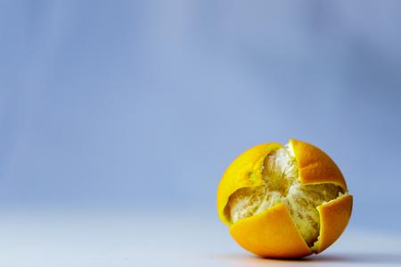 Whole orange on blue background with cut peel close up.