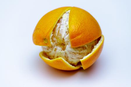 Whole orange on white background with cut peel close up