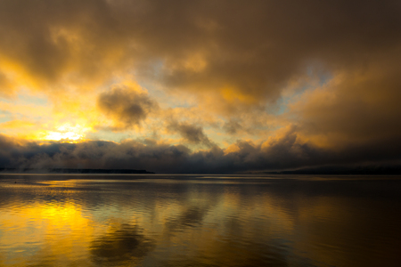 Sunrise on the lake, reflection of sun in water, with fog and clouds on summer morning