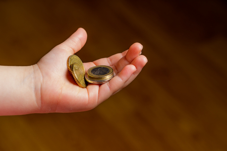 Child holding euro coin in his hand. Pocket money stock image. Poor low income group. Dark background. - Image. Close up Фото со стока