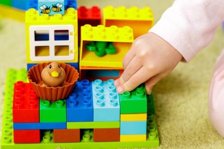 Children plastic color bricks with children hand. close up. Фото со стока