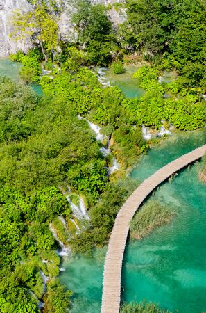 Beautiful view from the top of the blue lake in the summer afternoon in the national park of Plitvice in Croatia with wooden hiking trails.