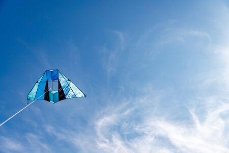 A kite in shades of blue in the wind on a blue sky with clouds. Feel the freedom