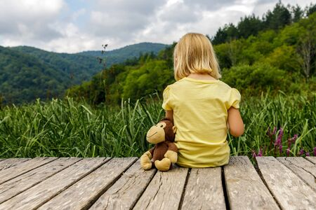 Little girl with monkey sits on wooden walkway and dreams. Tourism. Active family time in nature. Hiking with small children