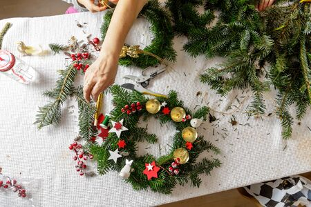 Hands of a woman make Christmas Advent wreath from fir twigs. Фото со стока