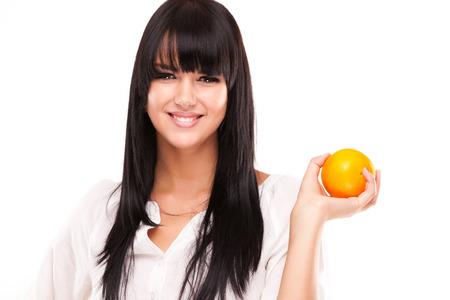 beautiful brunette woman with orange on white background Stock Photo