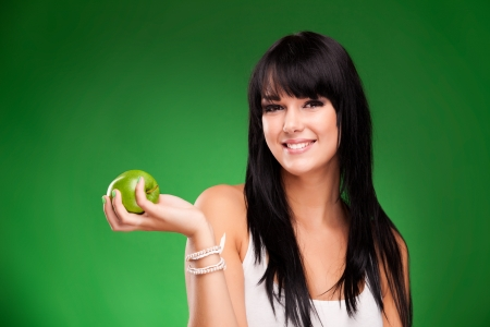 Cheerful beautiful brunette woman eating green apple, isolated over green background