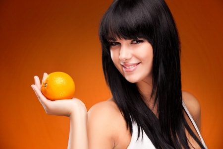 beautiful brunette woman with orange on orange background Stock Photo