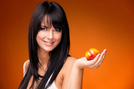 beautiful brunette woman with nectarine on orange background