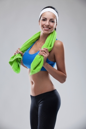 young smiling brunette woman after sportive exercise and holding the towel isolated on white  colored, retouched  Stock Photo